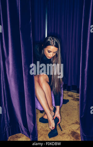 Young woman fitting high heels in a clothing shop - Stock Photo