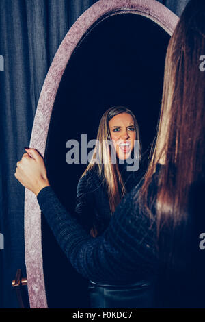 Mirror image of stressed young woman - Stock Photo