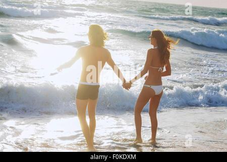 USA, Miami, young couple holding hands in front of the sea - Stock Photo