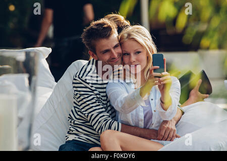 Young woman taking a selfie of herself and her boyfriend in an outdoor cafe - Stock Photo