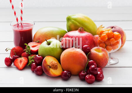 Different fruits and a glass of strawberry smoothie - Stock Photo