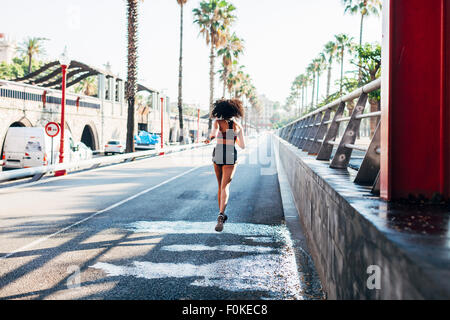 Spain, Barcelona, back view of jogging young woman on a street - Stock Photo