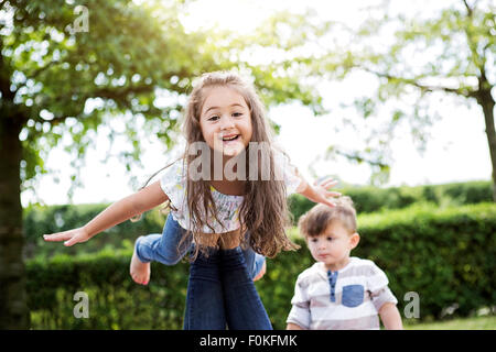 Portrait of little girl balancing on her mother's knee - Stock Photo