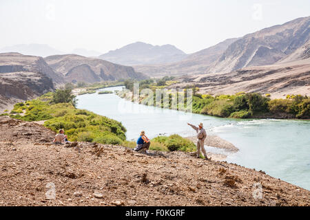 Tourists ang guide on the riverbank of Cunene River (or Kunene River) which forms the border between Namibia and - Stock Photo