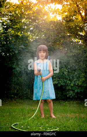 Toddler Girl Holding Water Hose Playing With Dog Stock