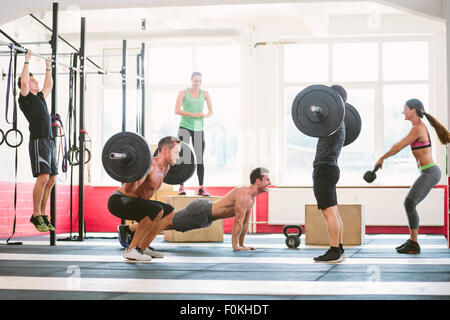 CrossFit athletes exercising in gym - Stock Photo