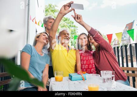 Three generations family taking a selfie on balcony - Stock Photo