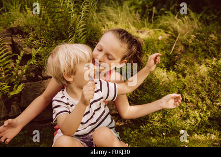 Girl and little boy playing in garden - Stock Photo