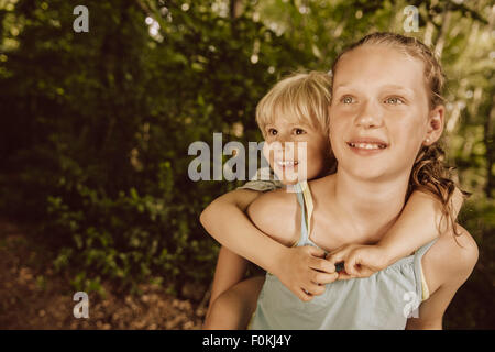 Girl carrying little boy piggyback through a forest - Stock Photo
