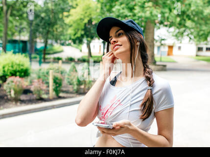 Portrait of young woman listening music with earphones in the park - Stock Photo