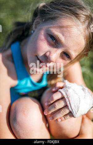 Portrait of blond girl with gauze bandage on her hand - Stock Photo