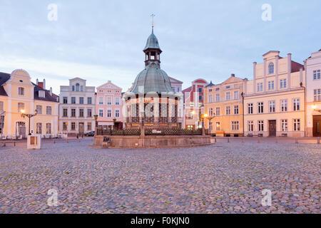 Germany, Wismar, market square with Wasserkunst at twilight - Stock Photo