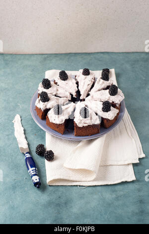 Sliced chocolate cake with creme and blackberries - Stock Photo