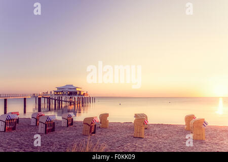 Germany, Niendorf, view to Timmendorfer Strand with hooded beach chairs and sea bridge - Stock Photo