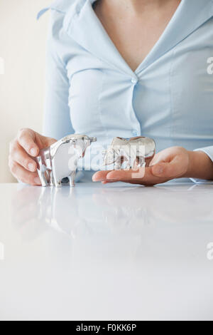 Close-up of woman's hands holding bull and bear figurine - Stock Photo