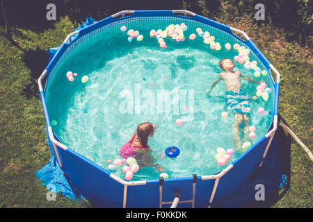 Boy and girl in swimming pool surrounded by balloons - Stock Photo