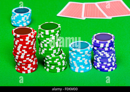 Stack of chips on the background of green the table. Cards in the background - Stock Photo