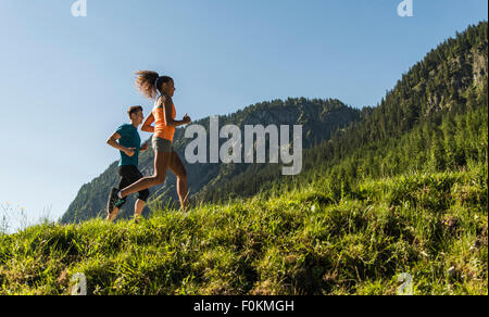 Austria, Tyrol, Tannheim Valley, young couple jogging in alpine landscape - Stock Photo