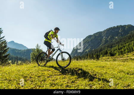Austria, Tyrol, Tannheim Valley, young man on mountain bike in alpine landscape - Stock Photo