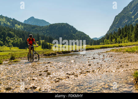 Austria, Tyrol, Tannheim Valley, young man on mountain bike crossing brook - Stock Photo