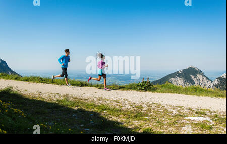 Austria, Tyrol, Tannheim Valley, young couple jogging in mountains - Stock Photo