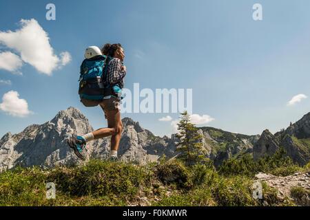 Austria, Tyrol, Tannheimer Tal, young woman hiking on mountain trail - Stock Photo