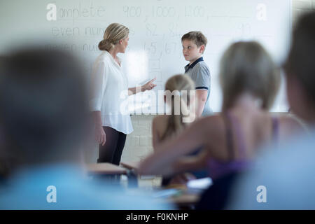 Teacher in classroom talking to schoolboy at whiteboard - Stock Photo