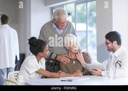 Senior couple at clinic talking to doctor and nurse - Stock Photo