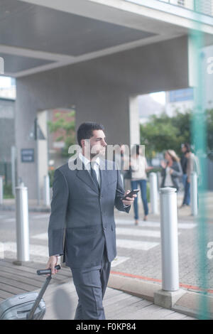 Businessman with suitcase and smartphone - Stock Photo