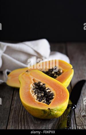 Cut papaya exotic fruit on a wooden table - Stock Photo