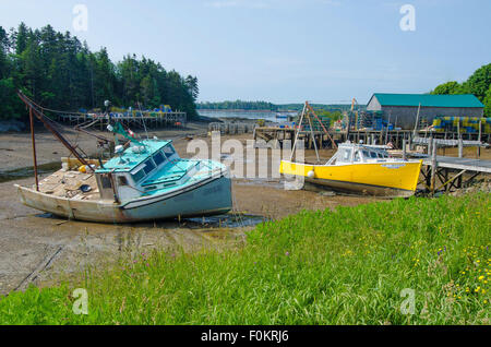 In this Maine harbor, lobster boats that are safely docked at high tide are stranded by low tide. - Stock Photo