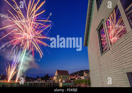 July 4th fireworks explode over a harbor on the Maine coast in celebration of Independence Day. - Stock Photo