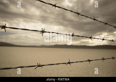 Barbed wire against cloudy sky over desert landscape in Nevada. Selective focus on barbed wire. - Stock Photo