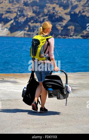 A woman carrying a baby carrier seat and a travel rucksack after arriving in the port Ormos Athinios Santorini Greece - Stock Photo