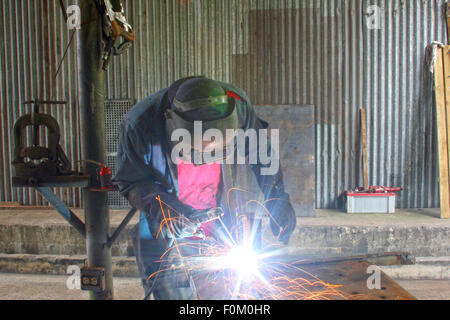 Man welding a piece of iron on a work table in a shop - Stock Photo