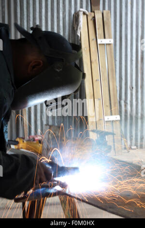 Man welding a piece of iron on a work table - Stock Photo
