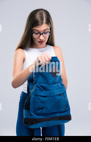 Portrait of a female teenager in glasses searching something in backpack isolated on a white background - Stock Photo