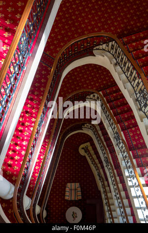Massive red old classic staircase see from above in Bilbao hotel with view on comfortable lobby, Spain. - Stock Photo