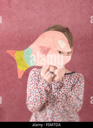Portrait of little girl in dress holding a cut out drawing of a fish in front of her face. She is shy and hiding - Stock Photo