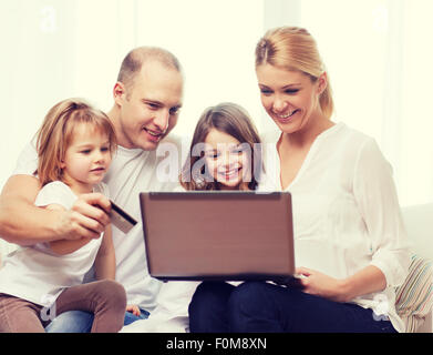parents and two girls with laptop and credit card - Stock Photo