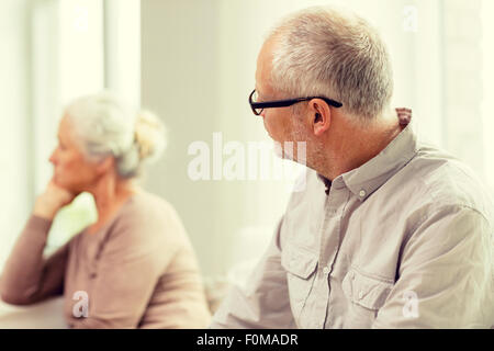 senior couple sitting on sofa at home - Stock Photo