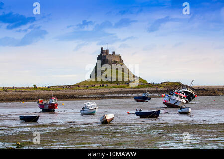 Skiffs at low tide in front of the castle on Holy Island, Lindisfarne, Northumberland, England, UK - Stock Photo
