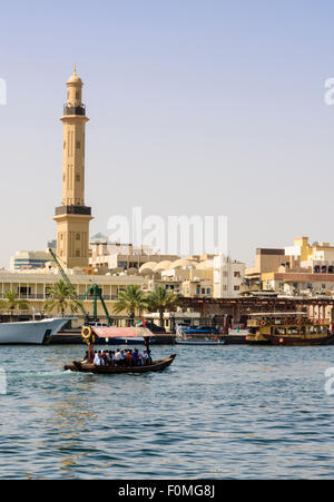 Abra boat with views over to the Grand Mosque Minaret, Dubai Creek, Deira, Dubai, UAE - Stock Photo
