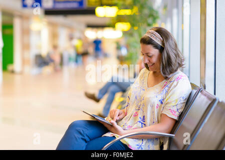 Young woman using a digital tablet in airport waiting area - Stock Photo