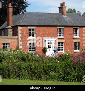 Eardisland Herefordshire man cutting lawn grass in elegant old red brick property UK - Stock Photo