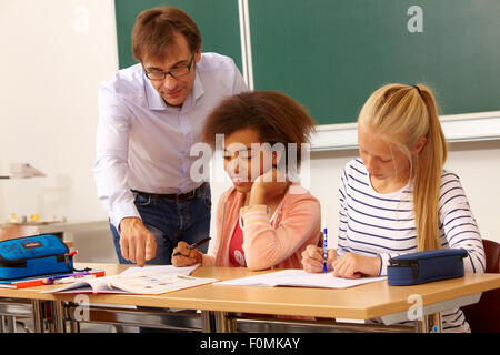 Teacher helps two schoolgirls in the lessons - Stock Photo