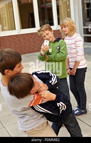 Cyber bullying in the schoolyard - Stock Photo