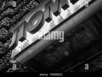 Red neon bar sign in Russian Language marks the entrance to a club - Stock Photo