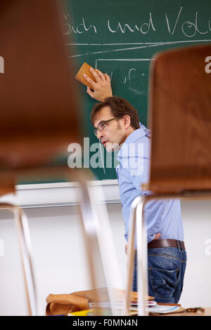 Exhausted teacher at black board - Stock Photo