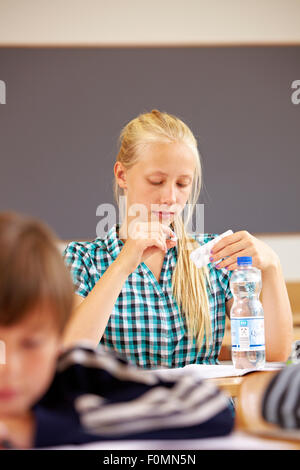 Girl in school takes a pill - Stock Photo